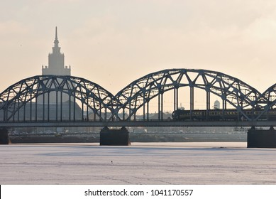 Railway bridge over the frozen Daugava river with view of the Academy of Sciences, Riga