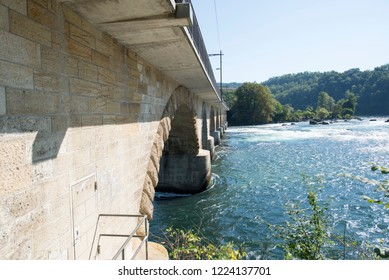 The railway bridge over The Rhine Falls.  The Rhine Falls is the largest plain waterfall in Europe. The falls are located on the High Rhine, near the town of Schaffhausen, Switz
