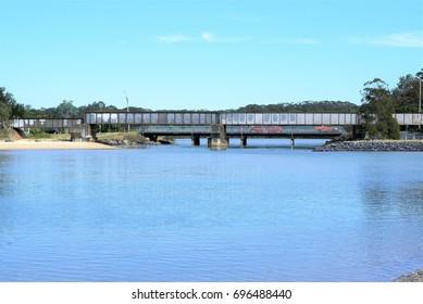 Railway bridge over river under blue sky. Railway bridge over creek in Australia. In far off distance are unrecognizable people and unidentifiable vehicles on road bridge.