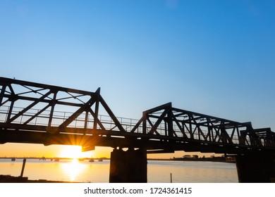 Railway bridge silhouetted by sunrise across Tauranga Harbour New Zealand.