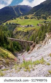 Railway bridge with the Swiss Alps and green pastures. Engadine, Switzerland, Europe