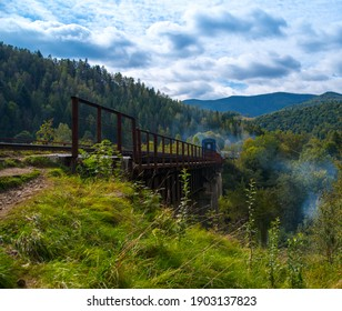 Railway bridge with train train high in the mountains in a beautiful mountainous area, green forest blue sky, mountain landscape, wallpaper, background, postcard