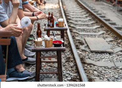 Railway cafe. People drink coffee or walking on railways waiting for train to arrive on railway road in Hanoi, Vietnam.