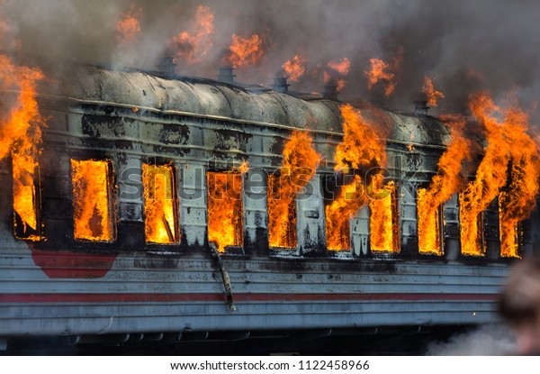 Railway carriage is on fire. Open flame. Firefighters fight with fire.