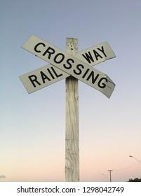 Railway crossing sign at dawn