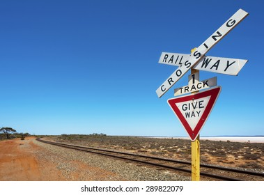 Railway crossing sign next to a long bend in the track.