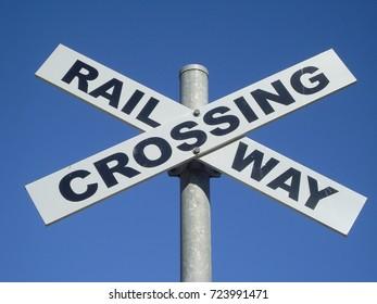 Railway crossing sign under blue sky