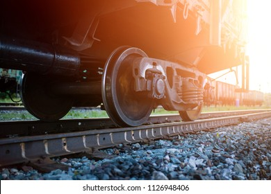 The railway engine of a freight locomotive that crosses the desert during sunset. Large transport of goods in tanks by rail. railway rails