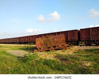 A railway freight train is passing through a ground while an oil wagons have been standing on ground derailed from tracks