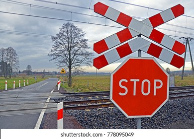 Railway level crossing with a saltire (Saint Andrew's Cross) and a stop sign