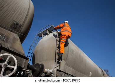A railway maintenance worker wearing hi viz clothing climbing a ladder onto a rail tanker to inspect the upper deck whilst working at height.