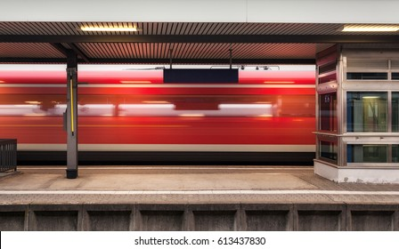 Railway platform with high speed red passenger train in motion in Germany. Blurred commuter train on railroad track. Railway station in the evening. Railroad travel and tourism. Industrial landscape