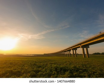 Railway or Railroad Bridge cross over green grass field in blue sky at Pasak Jolasid Dam during morning sunrise in summer, Lopburi, Thailand.
