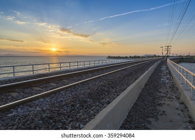 railway or railroad crossing the lake in the morning with the sunrise