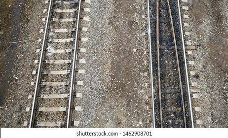 Railway, rails, two ways. Rails on concrete sleepers. Gray gravel is strewn around (small stones). View from above. Near the steel rail puddles after the rain. Travel concept, train trip, rest.
