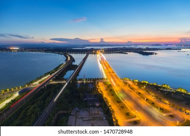 railway and road bridge leads to city through the lake, jiujiang cityscape in sunset, China