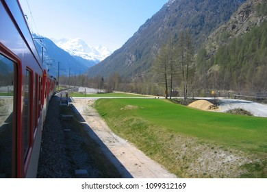 railway running along the mountain valley with steep rocky slopes and green lawns; scenic view of distant snowy peaks from the window of moving red passenger train, Swiss Alps