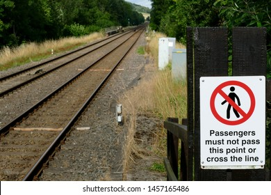 """Railway Sign, Showing a Symbol with words, """"Passengers must not pass this point or cross the line"""", with a Blurred rail track and Ecology Background."""