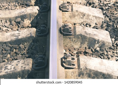 Railway sleepers and rails close-up. Iron bolts and connections. Railway background