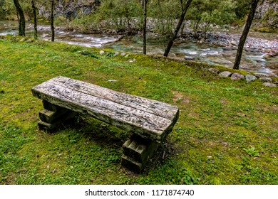railway sleepers for street furniture in the lawn at the edge of a mountain stream in autumn