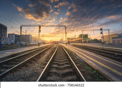 Railway station against beautiful colorful sky at sunset. Industrial landscape with railroad, blue sky with clouds in summer .Railway junction in the evening. Railway platfform. Transportation