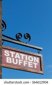 Railway station buffet sign against a clear blue sky