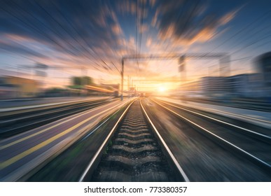 Railway station with motion blur effect. Blurred railroad. Industrial conceptual landscape with blurred railway station, buildings, blue sky with colorful clouds and sun. Railway track. Background