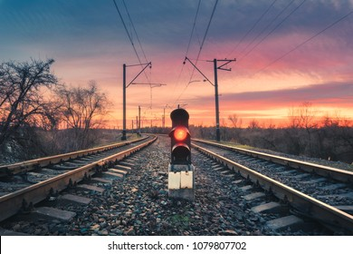 Railway station with semaphore against sunny sky with clouds at sunset. Colorful industrial landscape. Railroad. Railway platform with traffic light in the evening. Heavy industry. Cargo shipping