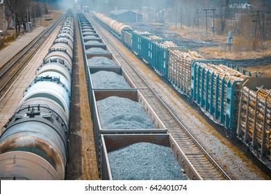 Railway stretches into the distance, three freight trains. carry wood, coal, fuel. Freight train, top view.