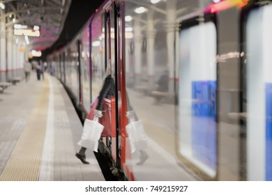 Railway subway station, at night, passenger train stopped. Unrecognizable girl enters train. Passenger transportation, style of life. Blurred background