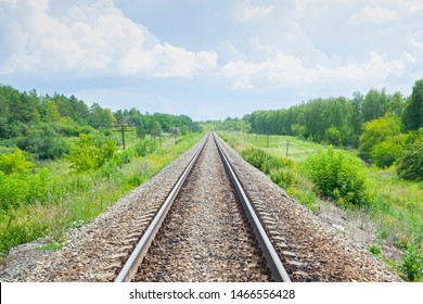 A railway through the summer green fields.  Beautiful green railway tree landscape sky clouds. Beautiful landscape. Railway transport.