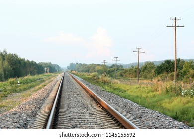 Railway track with a background of clouds and power poles in perpective
