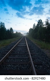 Railway track leading towards the center. Blue evening sky on the top and hint of fog in the horizon.