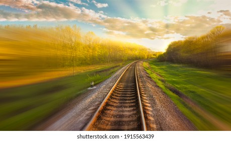 Railway track with motion blur effect. Blurred railway. Industrial conceptual landscape with blurred railway tracks and nature around. Blue sky with colorful clouds and sun. Railway.
