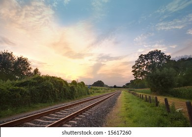 railway track in a rural landscape with sunset in the back