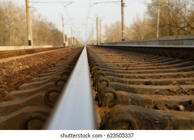 Railway track with sleepers goes into the distance, on the sides-poles for electric wires