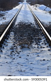 Railway tracks covered in snow. Railway to horizon. Railroad in winter morning. Railroad tracks in snow. Winter view of railroad tracks. Journey concept. Traveling concept.