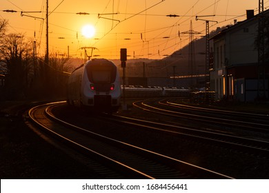 Railway Tracks in  a curve near Schwerte Ruhr Germany at sunset with local train, red lights, catenary, reflection in steel rails and glowing sun on a winter evening