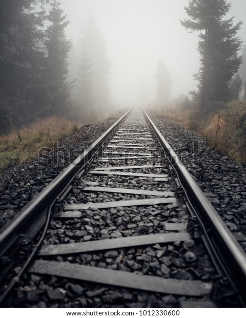 Railway tracks lead into dense fog