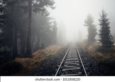 Railway tracks lead into a fog wall