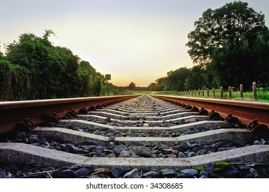 railway tracks with pale pastel sunset and frog point of view