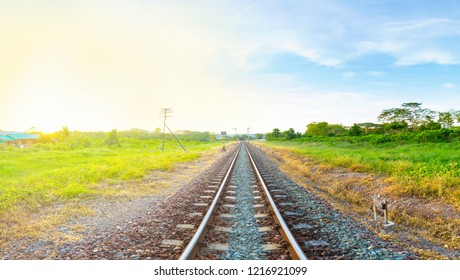 railway tracks in a rural area with bright moring sunrise, panorama view