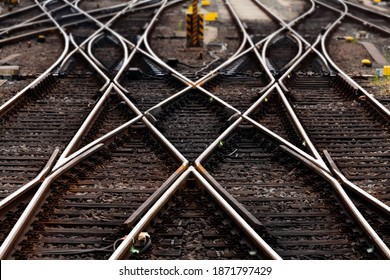 Railway tracks with switches and interchanges at a main line in Germany with symmetry and geometrical structures, lines and high contrast of rails, thresholds and  gravel