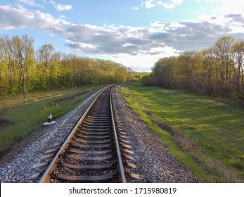 Railway, tracks through tree planting, green grass and beautiful nature, travel through Ukrainian steppes and forests.