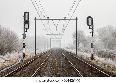 Railway tracks with traffic lights and overhead lines on a cloudy and misty day in winter, Utrecht, The Netherlands.
