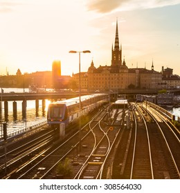 Railway tracks and trains near Stockholm's main train station in Norrmalm area, Stockholm, Sweden in sunset.  Silhouette of city hall and cathedral in background. Square composition.