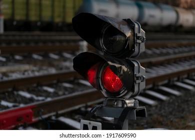 Railway traffic light on rails. Red light is on