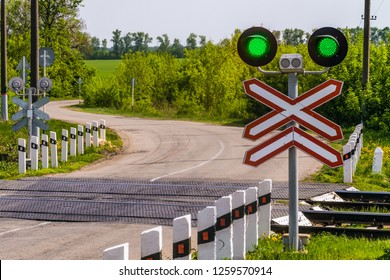 Railway traffic lights with a green signal. Railway and road crossing. Permissive Motion signal.