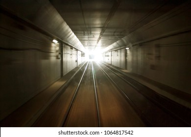 The railway in the tunnel, the train is moving at speed. Bright light at the end of the tunnel. Blur background