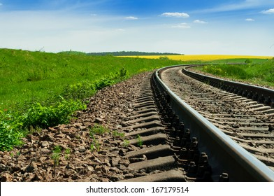 A railway turns upright through the spring green field. The sky is brightly blue with some white clouds